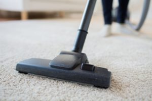 Lady vacuuming living room carpet