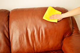 A ladies hand buffing a leather sofa after it has been cleaned.