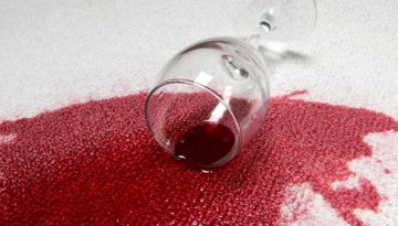 A glass of red wine spilled on carpet.